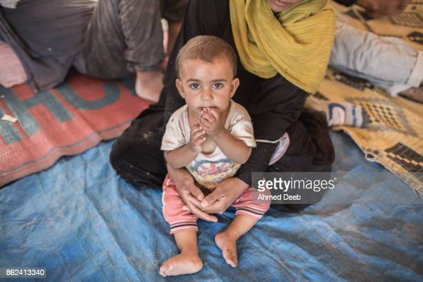 Woman who fled the Islamic State controlled area of Raqqa holds her child inside a tent at a makeshift camp of Ain Issa 50 kilometers north of Raqqa...