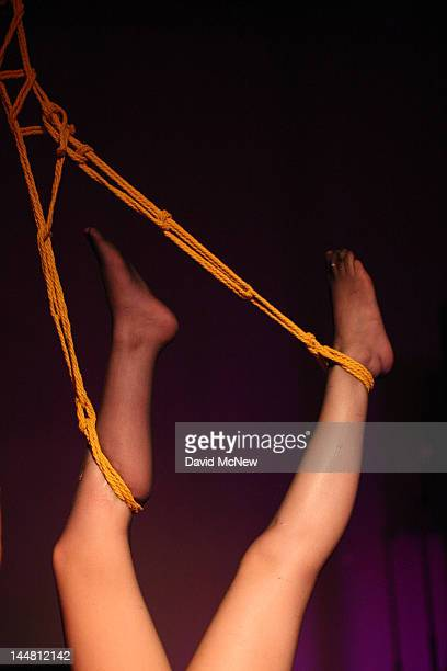 A woman who is a willing submissive participant is bound and suspended with ropes at a dungeon party during the DomConLA convention on May 18 2012 in...