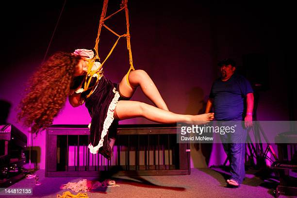 A woman who is a willing submissive participant is spun rapidly by Michael Sol as she is bound and suspended with ropes at a dungeon party during the...