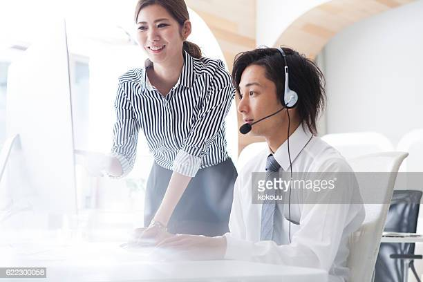 Woman who is instructing men at a call center