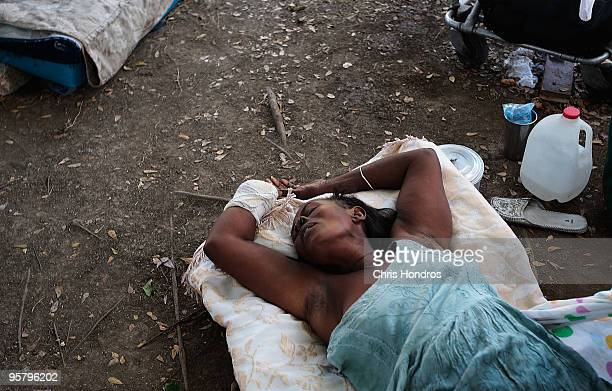 A woman who lost a hand lies on the ground outside at a makeshift recovery ward the morgue and main hospital on January 15 2010 in PortauPrince Haiti...