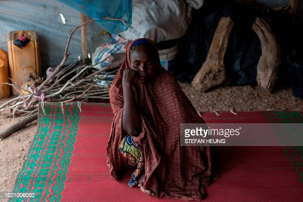 A woman who lost her family to Boko Haram sits on the ground in a tent in one of the IDP camps in Pulka on August 1 2018 As the presidential race...