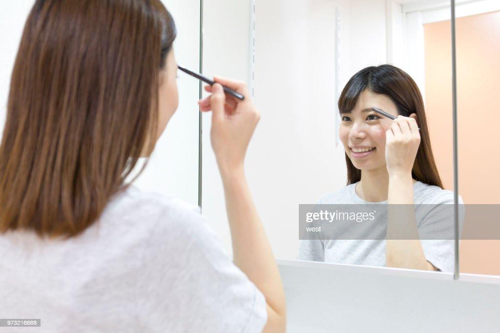 A woman who makes a makeup : Stock Photo