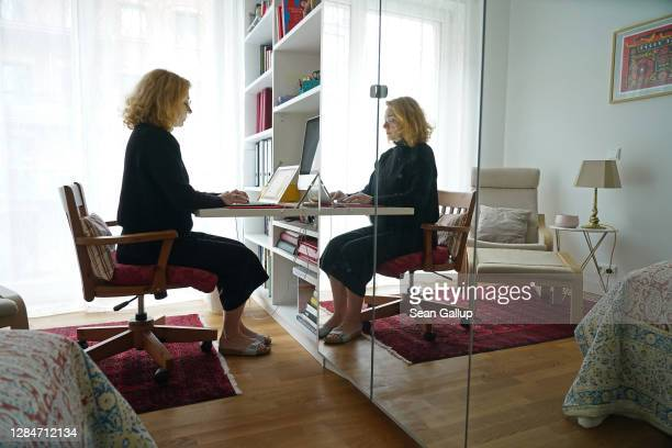 Woman who normally works in the office of a foundation works at her laptop from home in her daughter's room in home-office during a four-week...