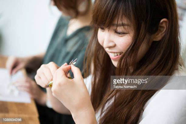 a woman who participates in a workshop and makes accessories - 女らしさ ストックフォトと画像