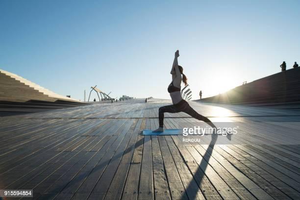 Eine Frau, die Yoga im freien spielt.