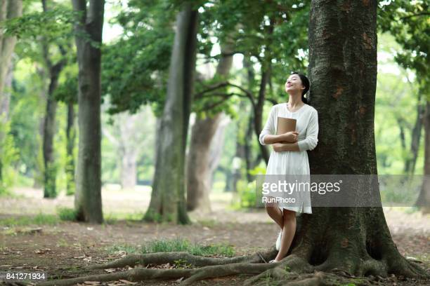 woman who raises a note at the park and is enjoying resting by closing his eyes