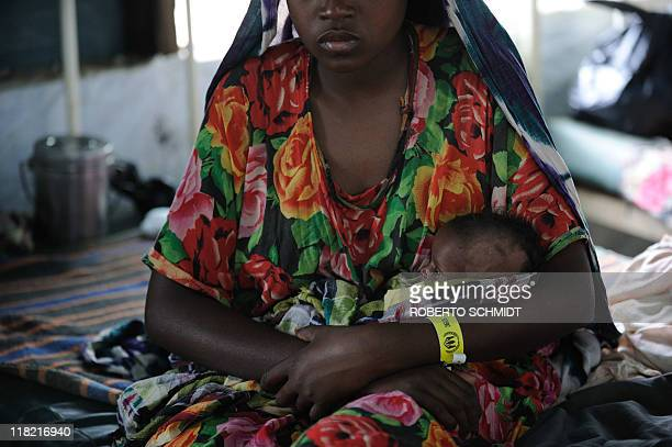 A woman who recently fled drought in Somalia holds her daughter in her arms at a clinic run by Doctors Without Borders at the worlds biggest refugee...