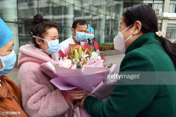 Woman , who recovered after being infected by a new coronavirus, receives a bouquet as she walks out of a hospital in Bozhou, in China's eastern...