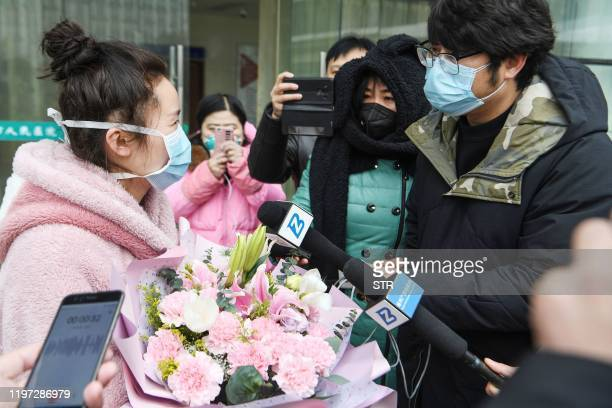Woman , who recovered after being infected by a new coronavirus, speaks to the press as she walks out of a hospital in Bozhou, in China's eastern...