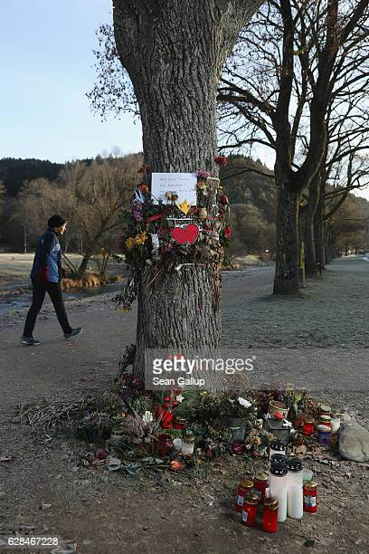 A woman who said she did not mind being photographed walks past flowers and messages left by mourners that adorn a tree near the spot where Maria L a...