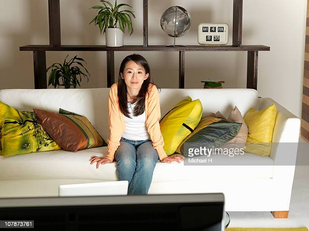 Woman who sits on sofa and watches television