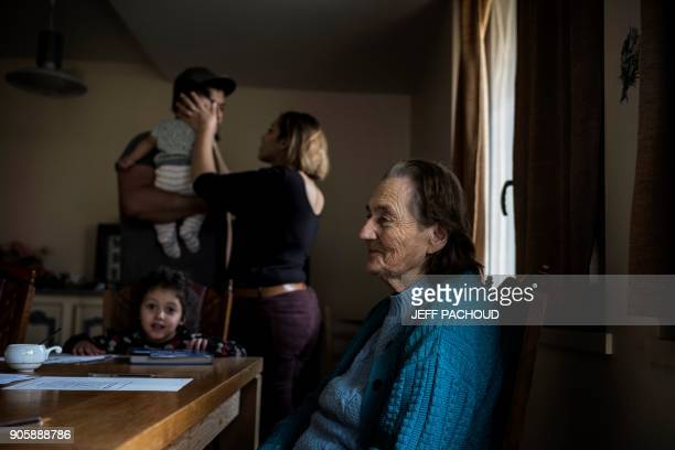 A woman who started to host people at her home two and a half years ago plays with her children next to an elderly woman who lives in her house on...