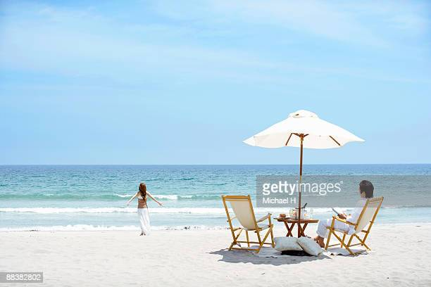 Woman who strolls and man who reads on beach