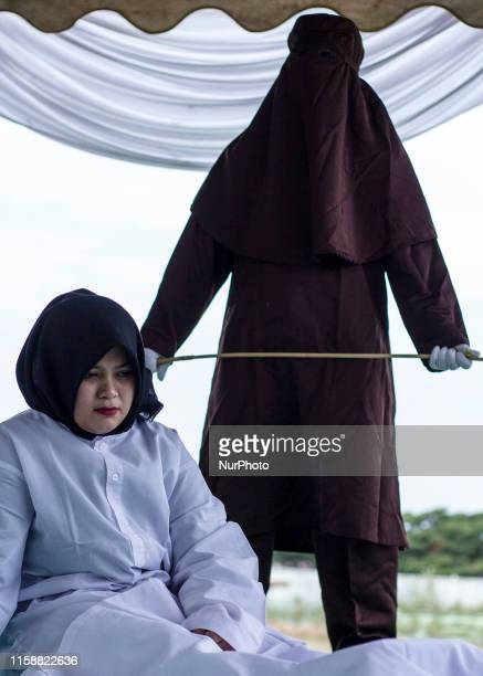 A woman who violated Islamic law sat in pain when flogged at a stadium in Lhokseumawe Aceh Indonesia on Wednesday July 31 2019 Three people violating...