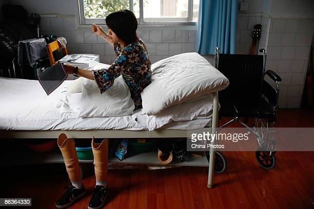 A woman who was injured in the Sichuan earthquake sews cross stitch in her bed at the rehabilitation centre of Sichuan Provincial People's Hospital...