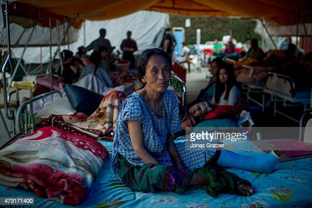 A woman who was injured in yesterday's earthquake rests in a bed in a tent outside of the Nepal Orthopedic Hospital on May 13 2015 in Kathmandu Nepal...