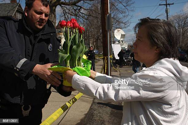 Woman who wished to remain anonymous gives flowers to a police officer for a memorial in front of the American Civic Association where, on April 3, a...
