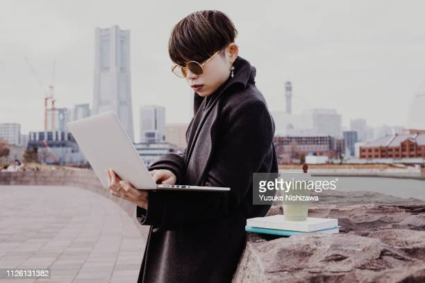 a woman who works outdoors on a computer - yusuke nishizawa stock-fotos und bilder