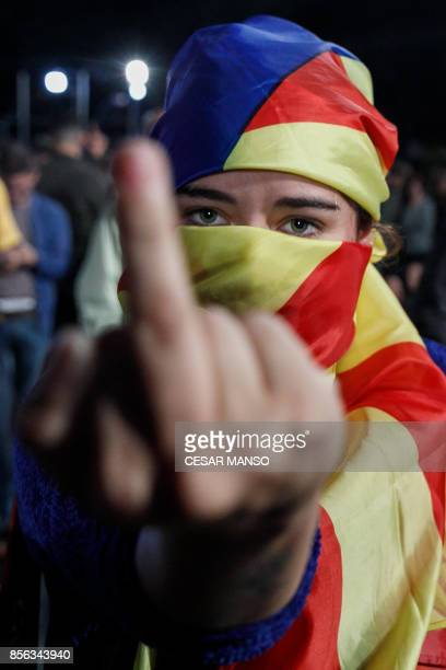 A woman whose face is covered with a Catalan proindependence flag gestures as people gather at Plaza Catalunya in Barcelona waiting for the results...