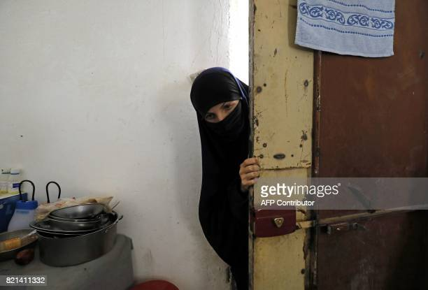 A woman whose family members are accused of being Islamic State militants enters a guarded building on July 22 2017 at a temporary camp for displaced...