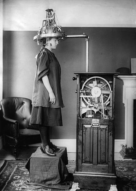 A woman whose head is attached to a machine which resembles...