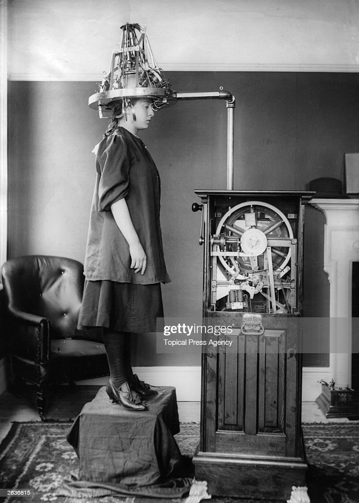A woman whose head is attached to a machine which resembles a large hairdryer, but is in fact a Lavery Electric Automatic Phrenometer, for measuring brain activity.