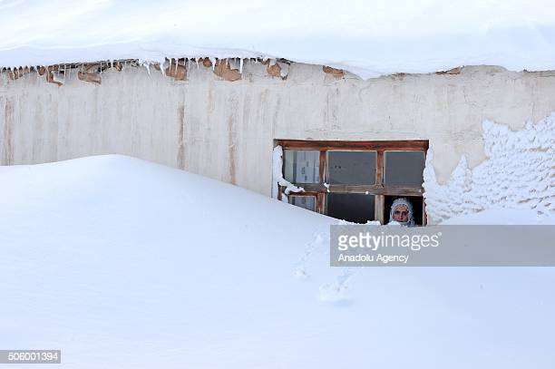 A woman whose house is covered with snow because of a night long heavy snowfall looks out of her window in the Gorentas neighborhood of Catak...
