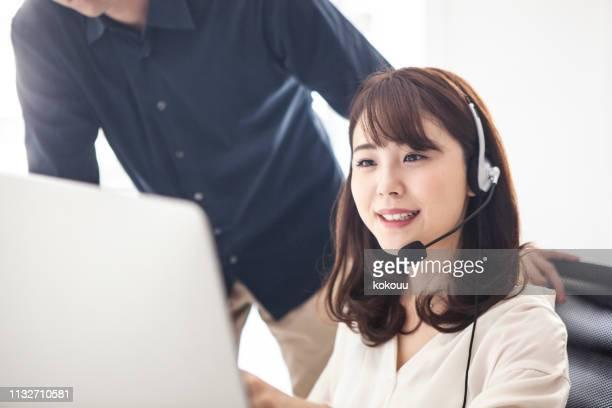 マネージャーがサポートコンテンツの女性顧客サポートを指示している女性 - 助ける ストックフォトと画像