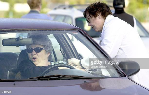 A woman winces as she receives a flu shot in her car at a drive thru flu shot clinic November 6 2001 in San Mateo California The annual clinic allows...