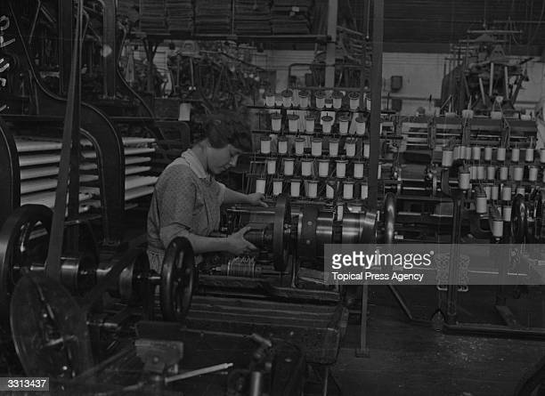 A woman winding bobbins in a lacemaking factory