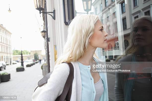 Woman window shopping on city street