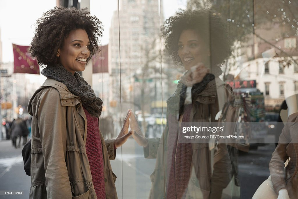 Woman window shopping on city street : Stock Photo