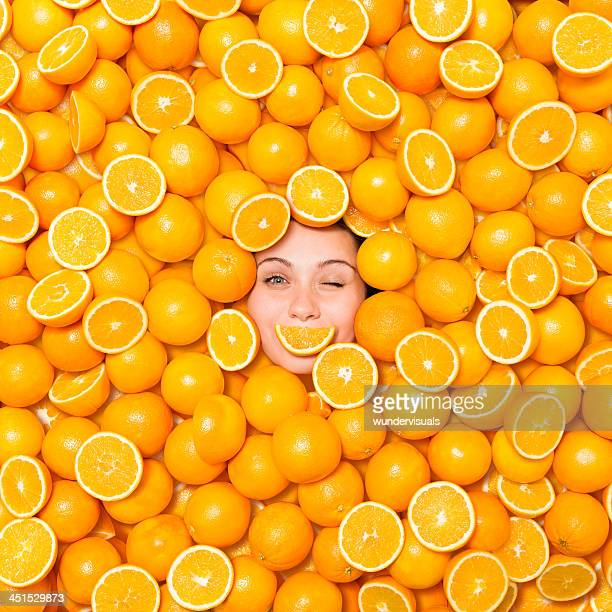 woman winking surrounded with oranges - orange colour stock pictures, royalty-free photos & images