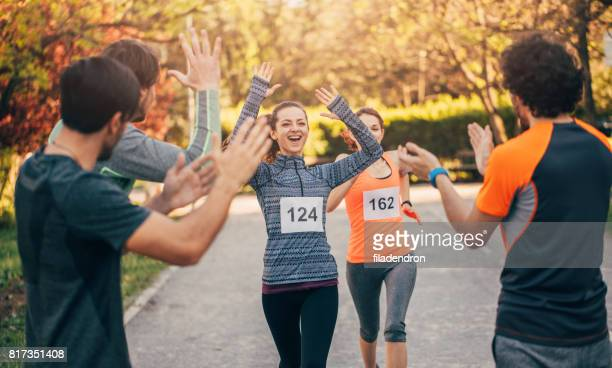 woman winning a running race - attending stock pictures, royalty-free photos & images