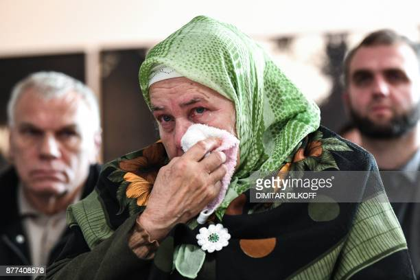 TOPSHOT A woman wipes a tear as she gathers with others including relatives of victims of the 1995 Srebrenica massacre to watch a live TV broadcast...