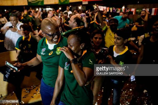 A woman wipes away her tears as South Africans celebrate after South Africa won the Rugby World Cup 2019 Final between South Africa and England at...