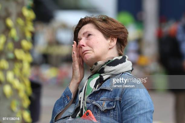 A woman wipes away tears as she look up as Grenfell Tower on the one year anniversary of the Grenfell Tower fire on June 14 2018 in London England In...