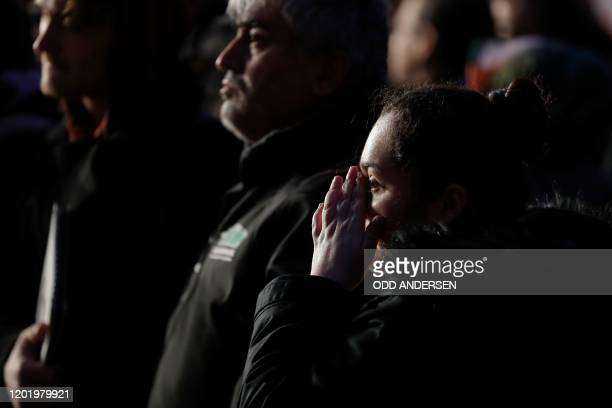A woman wipes her eye during a vigil close to a crime scene in Hanau near Frankfurt am Main western Germany on February 20 after at least nine people...
