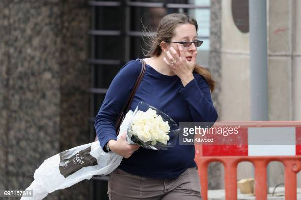 A woman wipes her face as she carries flowers to London Bridge the scene of last night's terror attack on June 4 2017 in London England Police...
