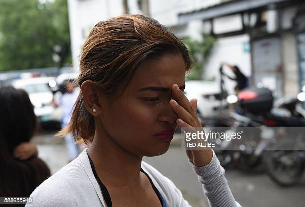 A woman wipes tears as she tries find out if a relative is one of 10 inmates killed during an attempted jail break by other prisoners in Paranaque...