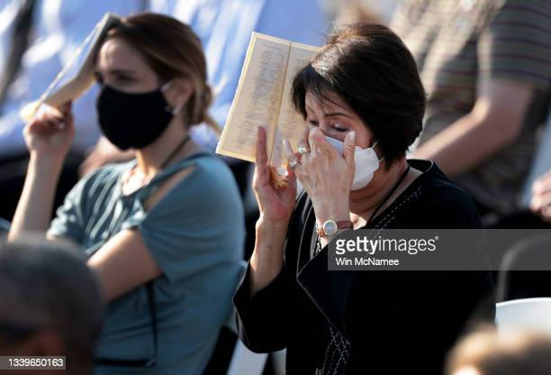 Woman wipes tears during a moment of silence during the Pentagon 9/11 observance ceremony at the National 9/11 Pentagon Memorial on September 11,...