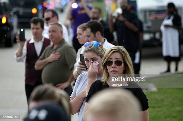 A woman wipes tears from her eyes as she watches with other mourners as the funeral procession for Baton Rouge Police Officer Matthew Gerald leaves...