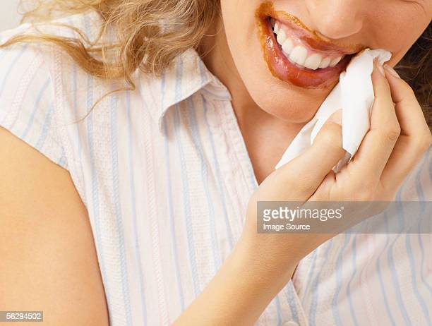 Woman wiping chocolate from mouth