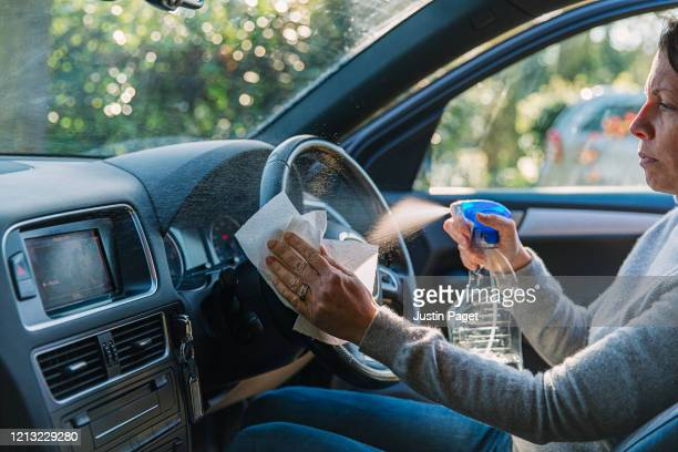woman wiping down car steering wheel - cleaning stock pictures, royalty-free photos & images