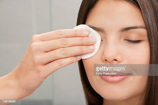 Woman wiping eye with cotton pad
