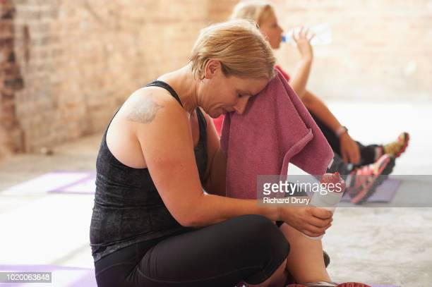 woman wiping her forehead with a towel in the gym - real body fotografías e imágenes de stock