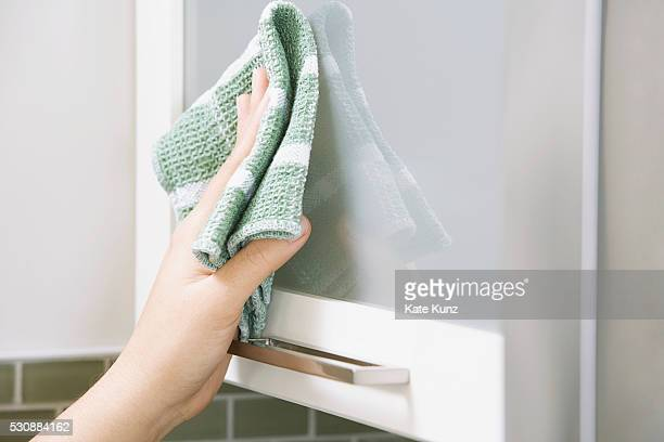 Woman wiping kitchen cabinet