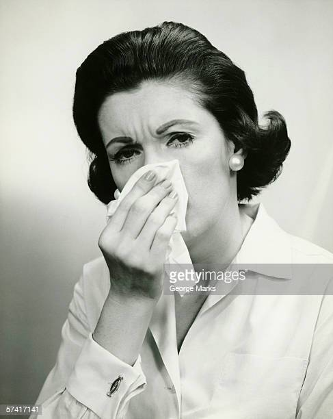 Woman wiping nose with handkerchief, (B&W), (Portrait)
