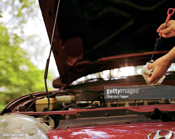 Woman wiping oil from car dipstick, close-up